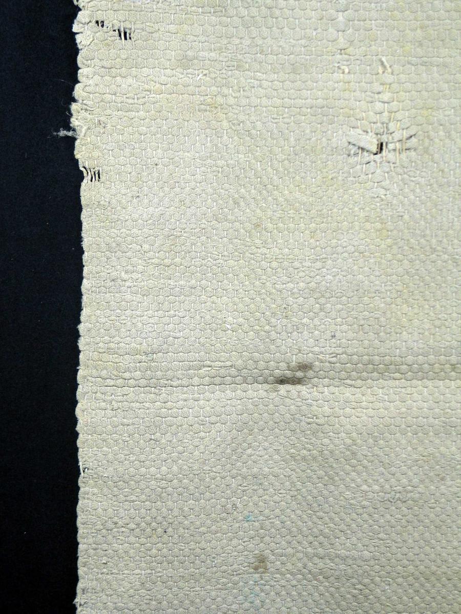 Beige rye med vevbredde på 93 cm. Faldet i kortsidene.