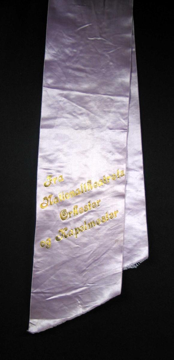 Begravelsessløyfe i lilla silke med tekst i gull.