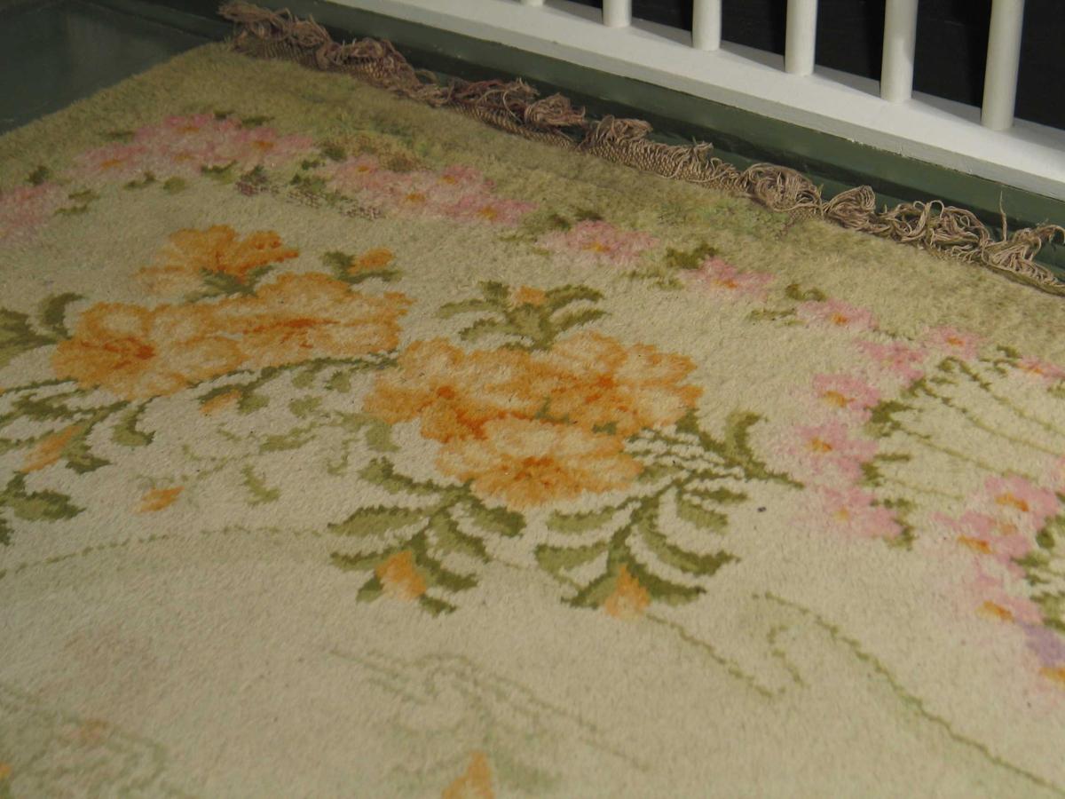 Blomstret golvteppe med flossknuter i fargene beige, lys grønn, mørk grønn, rosa og gult. Hovedformen på midtpartiet er rektangulært, men med store buer i hjørneavrundingene og noe innsvinget i sidene. Konturen rundt er lys grønn og smal. Gul blomst med grågrønne blad i horisontale striper, spredt utover men vendt mot midten. Teppets hjørnemotiv er store gule blomster og grønne blad som strekker seg noe inn fra midtpartiet. Midt på hver side en innovervendt palmett eller vifteform av smale grønne buete linjer som ender i en halvsirkelformet rosa blomsterkrans. På langssiden gul blomsterranke på hver side. På korstsiden opppoverbuet blomsterranke. Fra bunnen av viftene løper en rosa og grønn guirlander med et ensfarget lys grønt felt, 10-20 cm felt ut til jare og  9 cm lange frynser av renningen. Mellom hver rad smyrnaknuter er det to innslag rødbrun hamp.