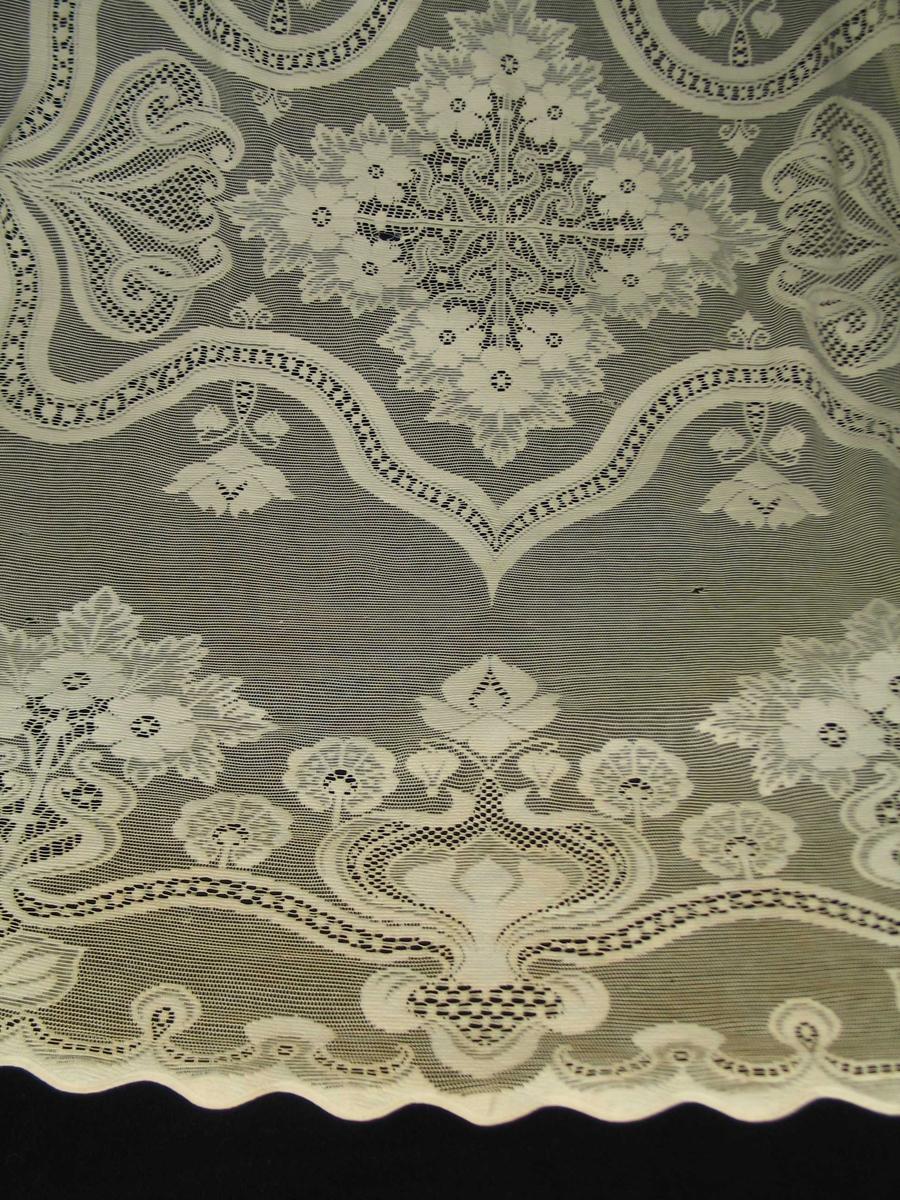 Vevd som avsluttet enhet. Tunget ytterkant kantet med diagonalvevd bånd. På gjennombrutt bunn, store, stiliserte frittstående blomster med et bølgete bånd som holder sammen figurene og som slynger seg i store buer i hjørnene. Fritt, midt på teppet en speilvendt symmetrisk form med spisser og buer, 118x86 cm. Rombisk helsymmetrisk blomsterfigur i midten, 3 og 3 utovervendte blomster med blad.