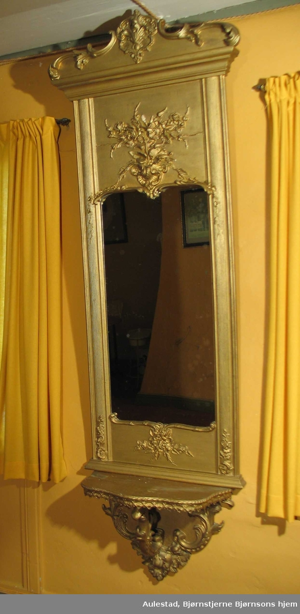 Speil i rokokkostil med rose- og rocailleornamenter. Forgylt overdel med akantusskjæring.