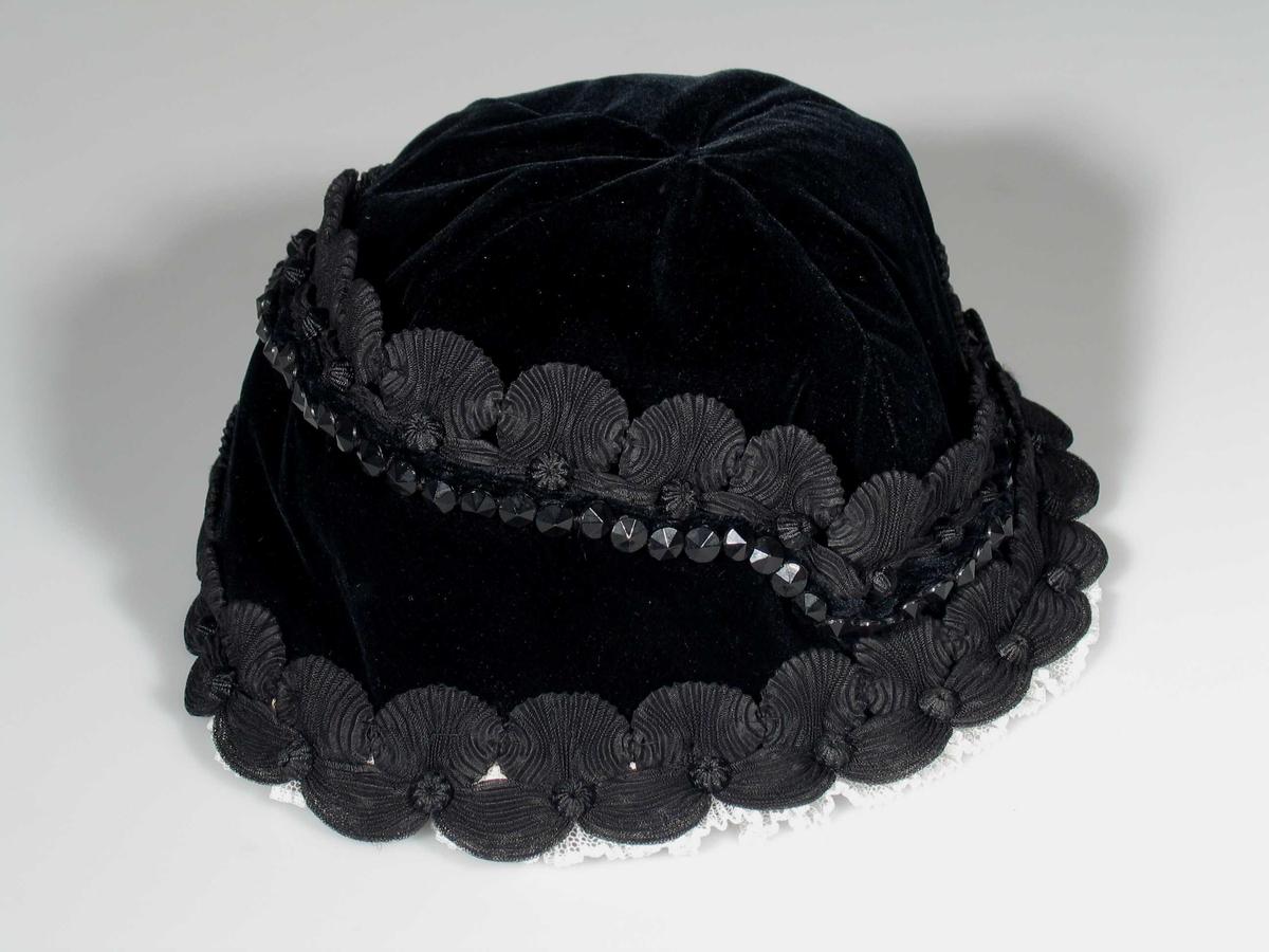 Svart hatt i fløyel kantet med plisserte bånd og steiner. Foret med svart silke.