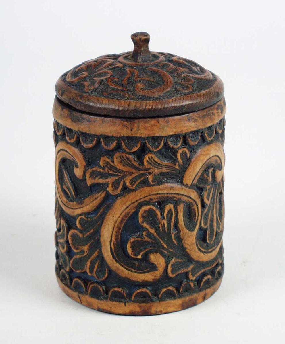 En tobakksdåse i bjørk med lokk. Den er malt i svart og blå farge. Tobakksdåsen har utskjæringer i form av oppløst ranke med rikt bladvekster. Lokket har påfestet en liten firkantet knott.