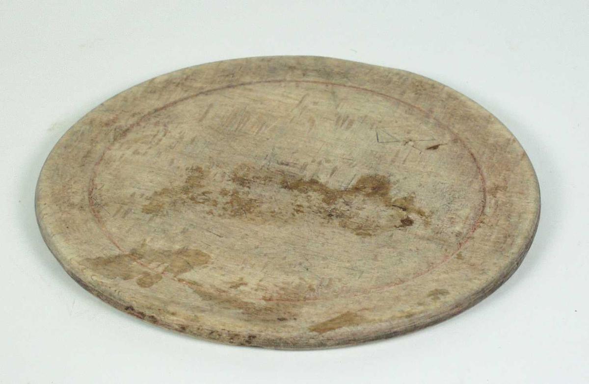 Dreid tallerken i bøk. Under er det skåret inn trolig et buemerke og initaler.