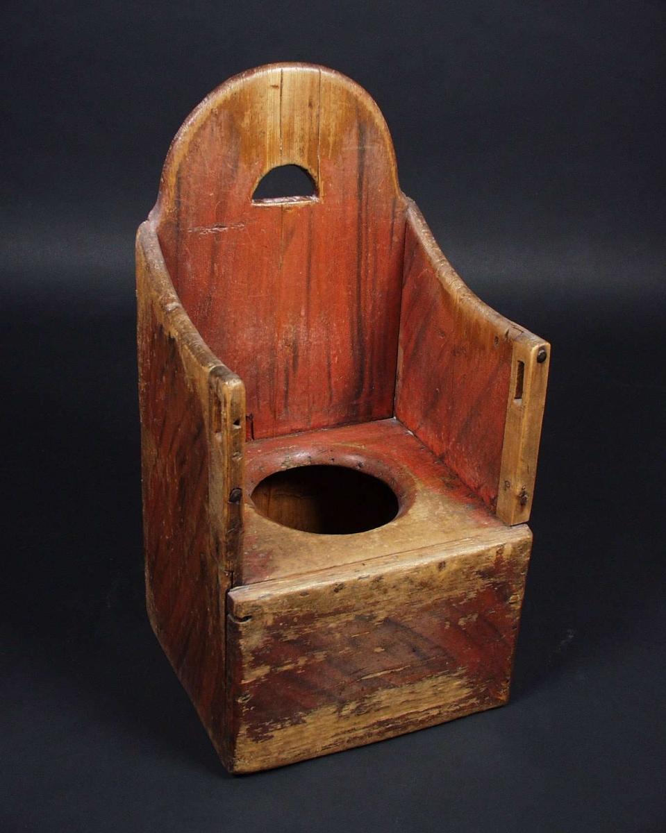 Barnestol med hull i setet. Lokk hører til. Stolen er laget av tre og malt rødbrun med sorte flammer. Øverst på karmene foran har det vært en list. Listen mangler.