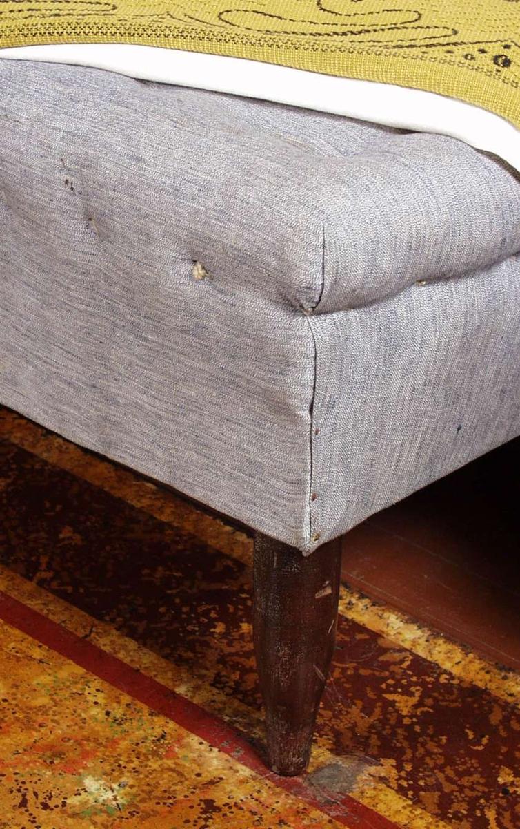 Divan med dreide bein og polstret grå madrass som er stiftet til rammen. Divanen er opphøyet på den ene siden.