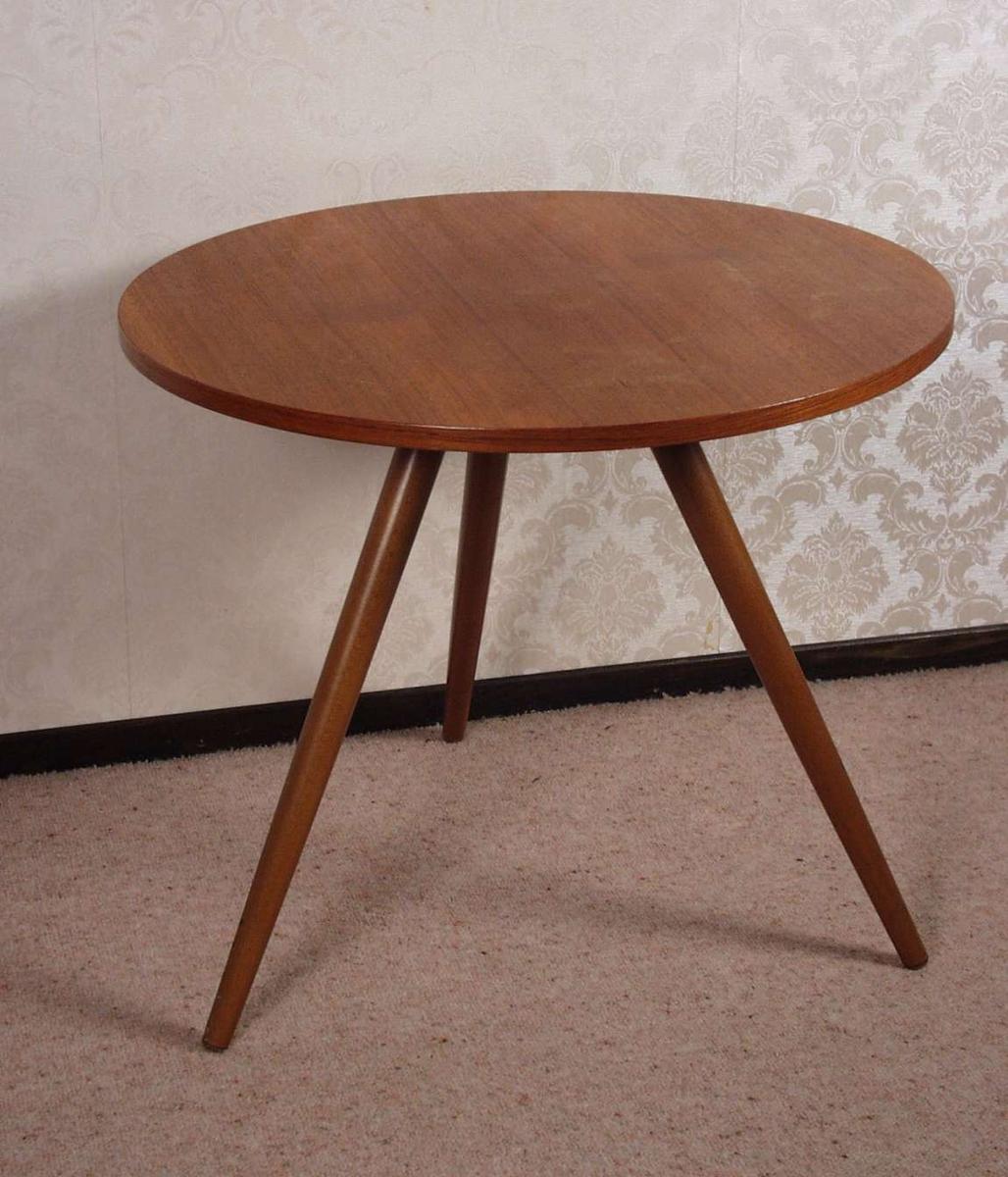 Rundt lite bord i teak med tre ben som skrår ut fra midten av bordplaten.