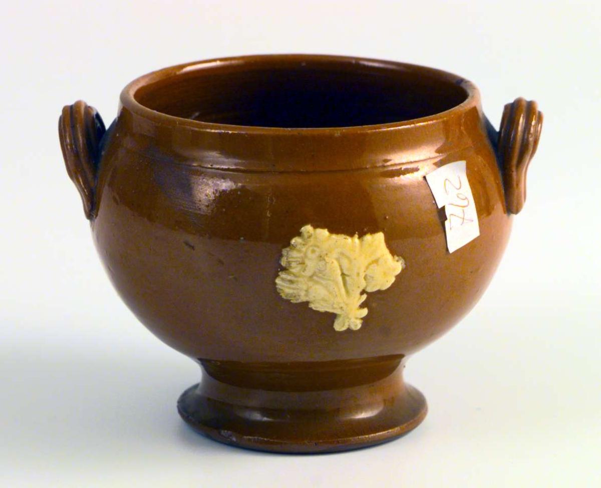 Sukkerkopp i brun keramikk. Den har to små hanker. Den er dekorert med påsatt, gul blomsterdekor som er litt defekt.