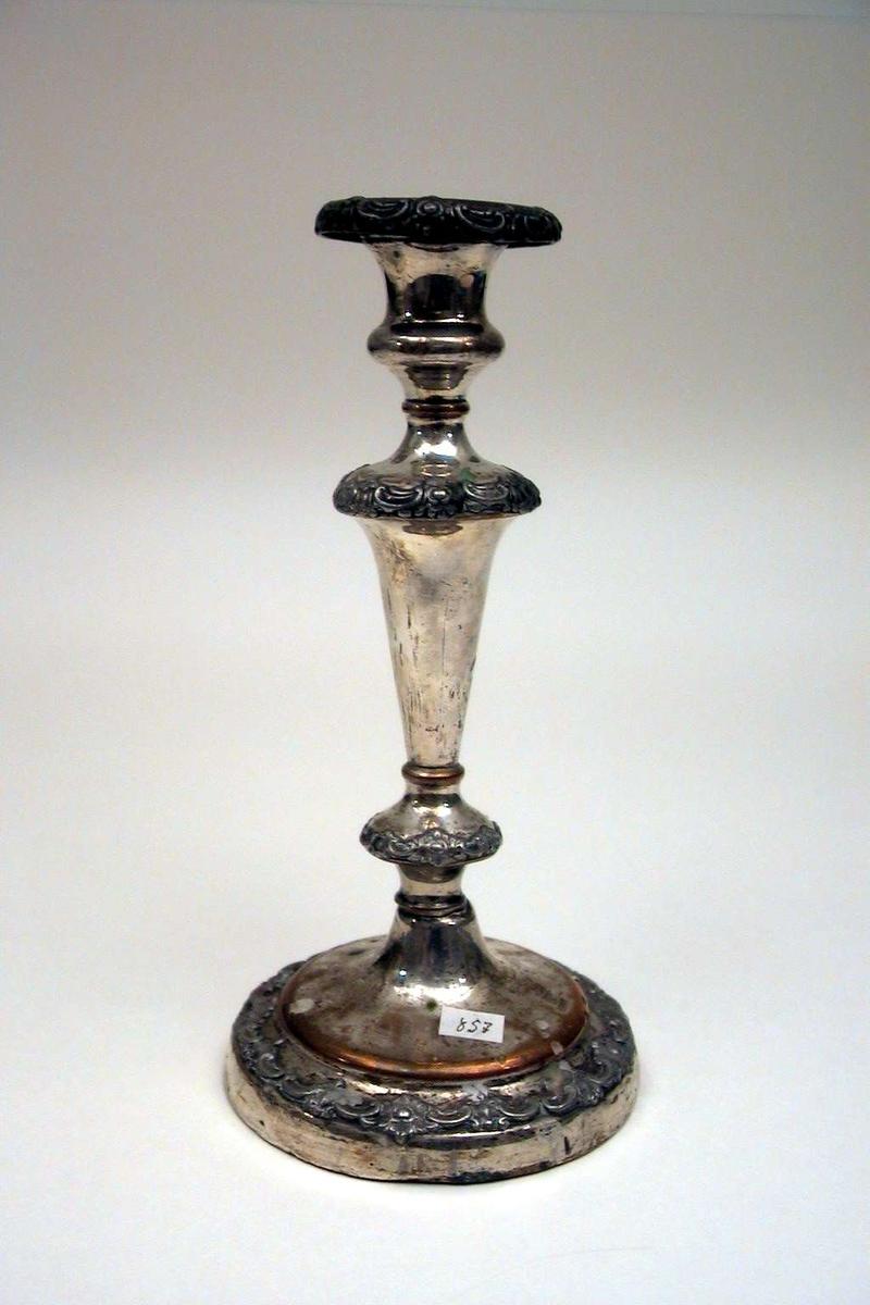 Lysestake i sølvplett. Kobberet skinner i gjennom flere steder. Staken har rund fot. Staken har dekor i relieff.