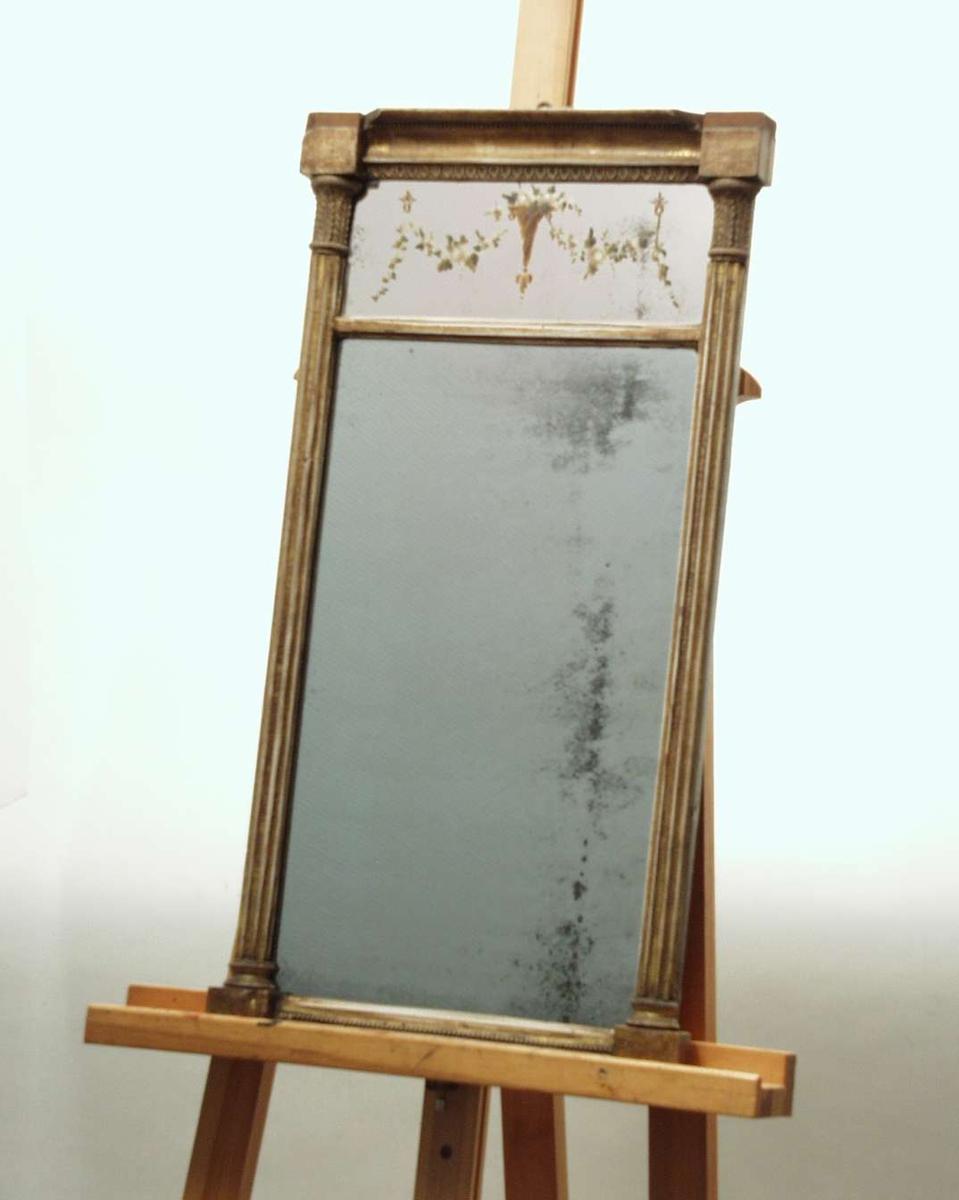 Speil med ramme i empire. Rammen er av tre. Sidene er formet som pilastre. Speilflaten er delt i to. Øverste del er dekorert med girlandere. Rammen har vært forgylt og polert.