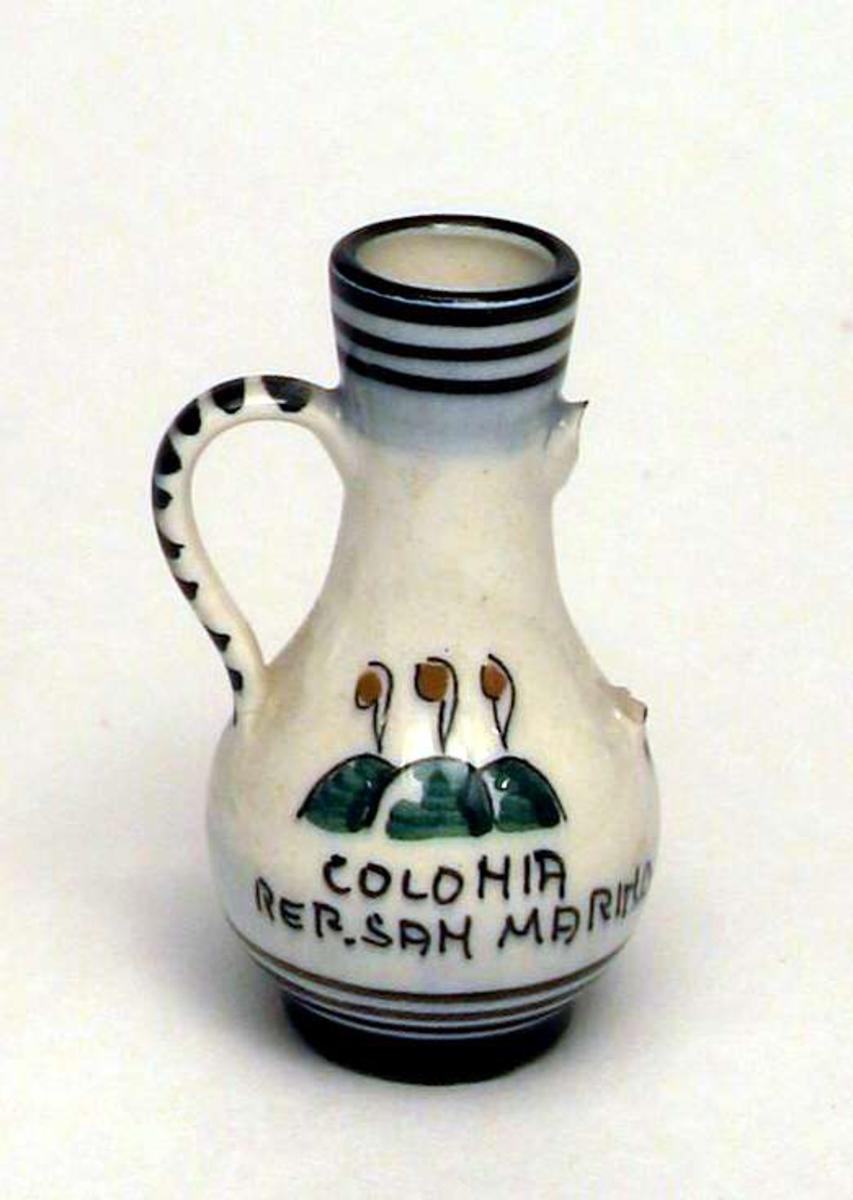 Liten krukke med to hanker og smal hals. Den ene hanken mangler. Krukken er dekorert med sorte ringer rundt hals, ved foten og på hanken. Det står skrevet Colonia Rep. San Marino på krukken.