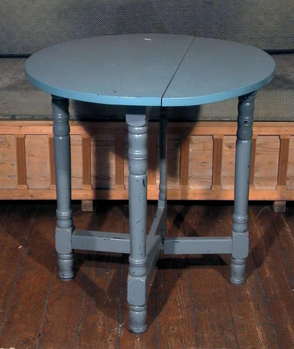 Rundt klaffebord med fire ben og benforsterkning. Bordet er bondeblått.