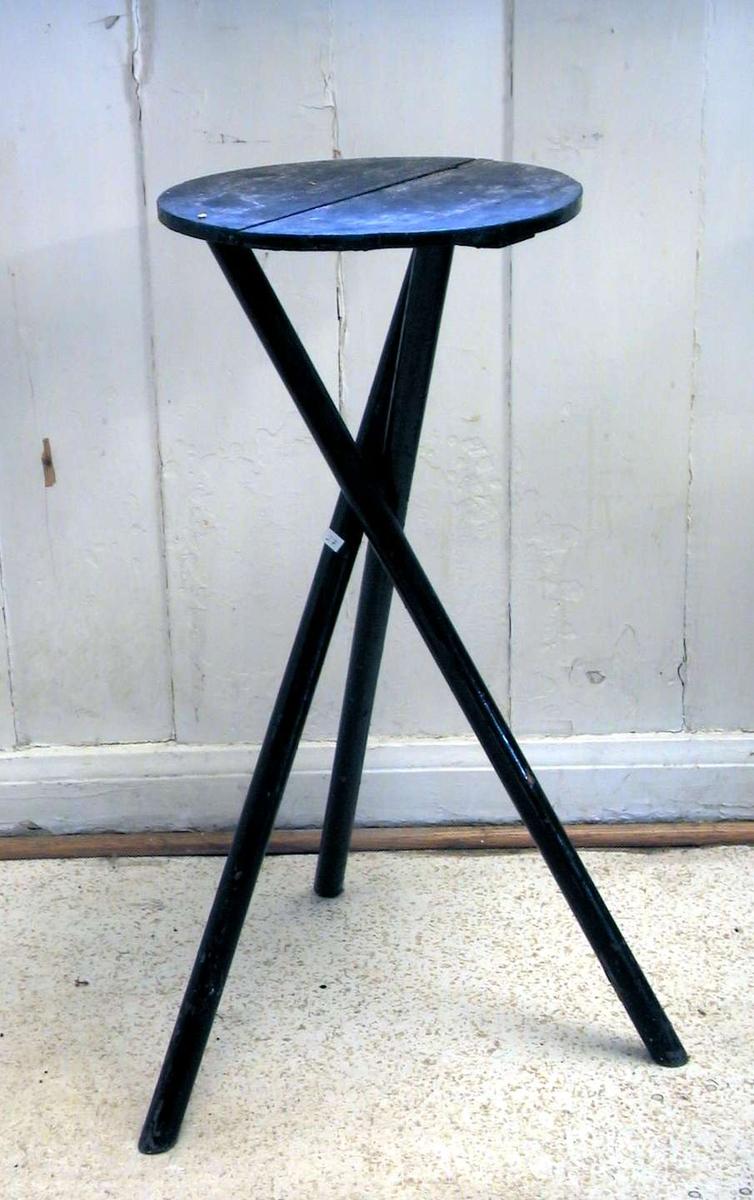 Sort blomsterbord på tre krysstilte ben. Platen er rund. Bordet ser hjemmesnekret ut.