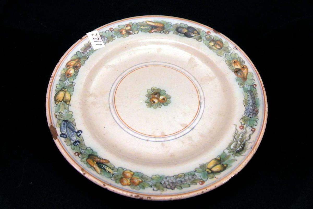 Asjett med håndmalt dekor. Dekorert med frukter, nøtter og rakler i en ring rundt kanten og midt på asjetten. Det er hakk i kanten av asjetten.