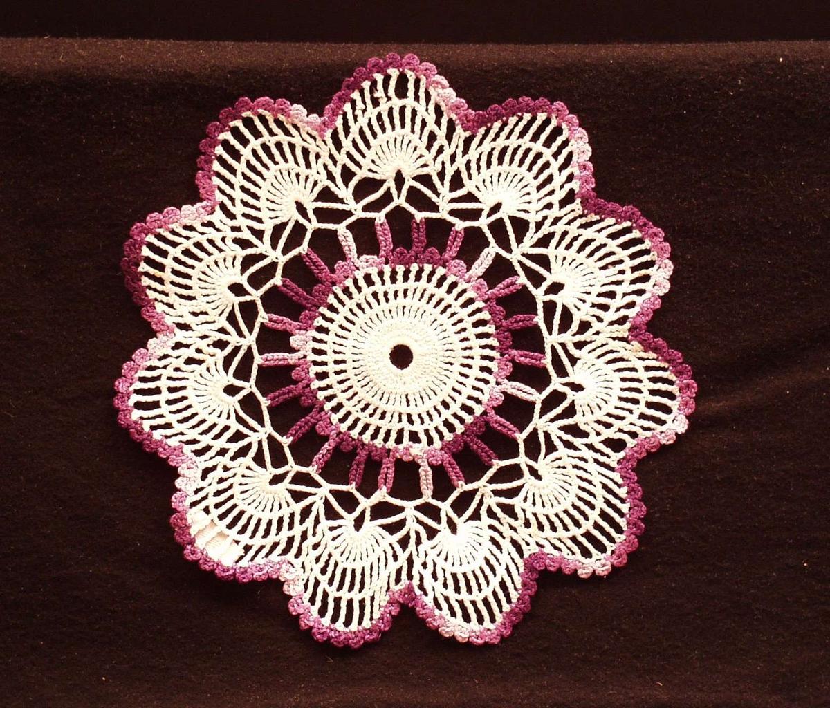 Hvit og fiolett heklet brikke med midtrosett og tunget ytterkant.