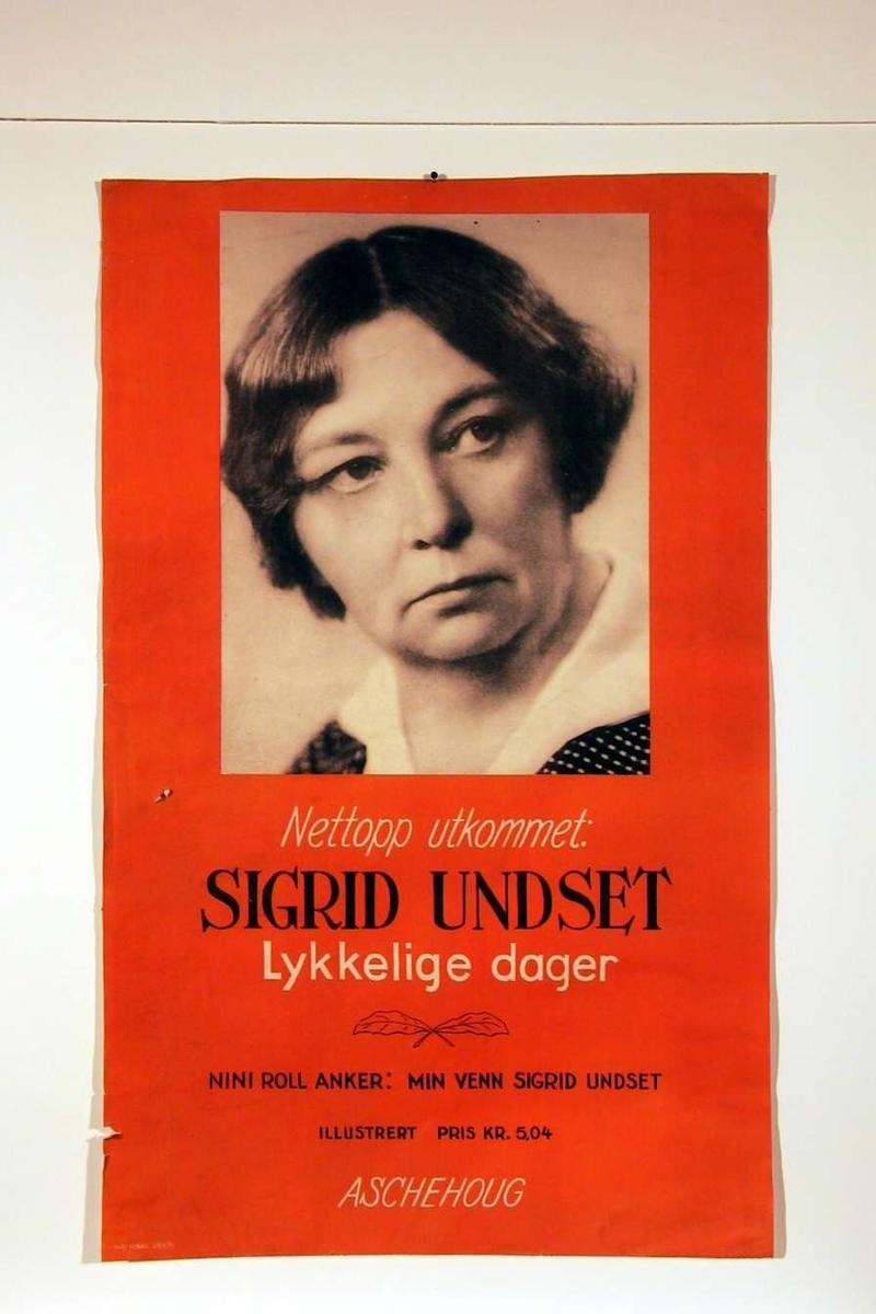 En plakat som reklamerer for S.U.s minnebok 'Lykkelige dager'. Plakaten har også et portrettfotografi av S.U..