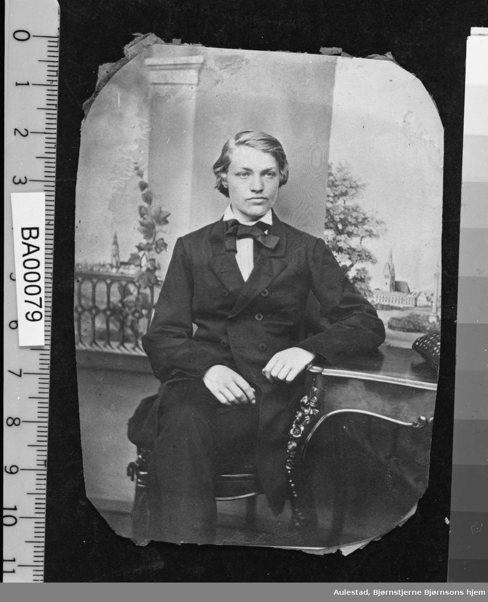 Portrettfotografi av ung mann med halvlangt lyst hår, sittende med benene i kors, kledd i mørk dress med halsbind.
