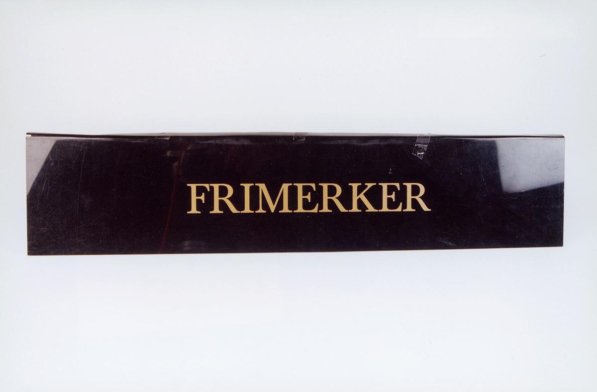 Lukeskilt i svart plast med gullbokstaver: Frimerker ex