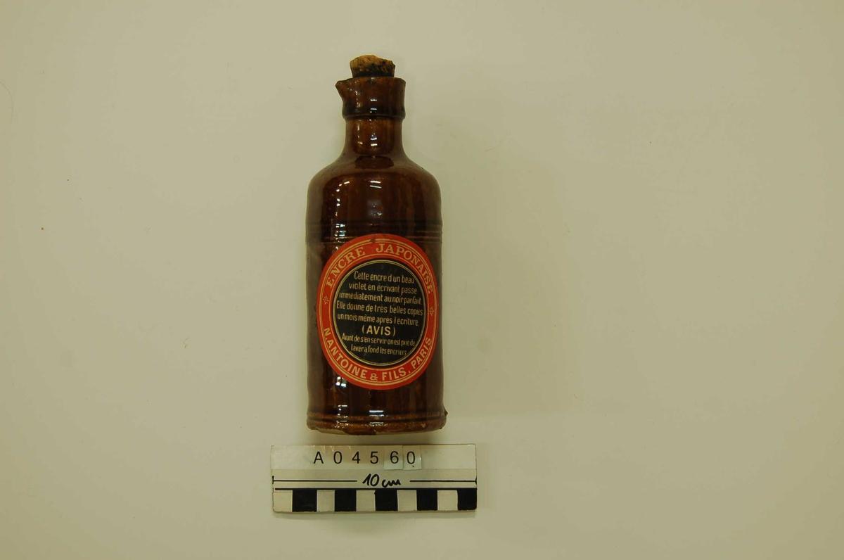 Brun keramikkflaske med helletut. To påklebede etiketter. Korken er brukket, innholdet tørket til klumper.