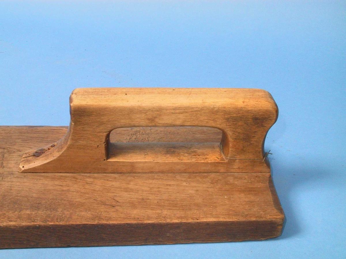 Høvlet, avskrådd kant, innfelt og skrudd handtak. Enkel form, ingen dekor. Skruene er trolig sekundære.  Avsmalnende, breiest foran, smalere bak. Enkelt håndtak