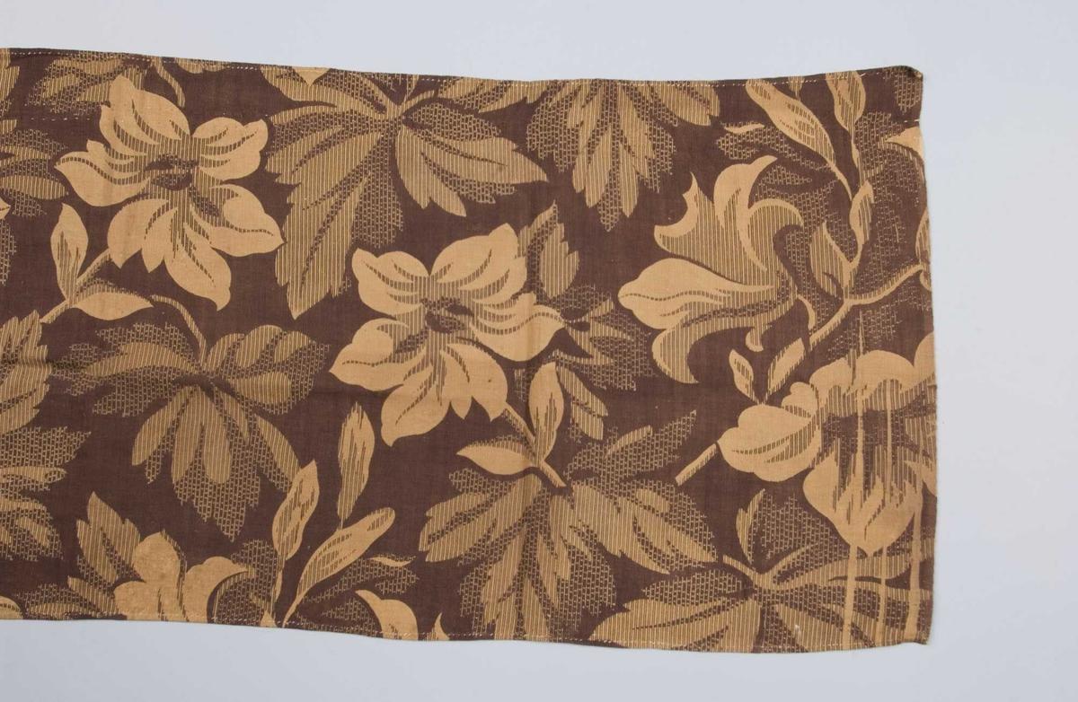 Rektangulært stykke, sydd sammen av to stykker med motsatt mønsterretning, håndsydd. Trykket mønster u to farger, store blomster. Rester etter opphenget.