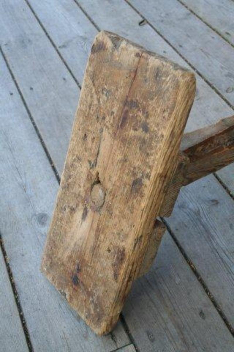 Kort plankestubb med to trestykker spikret til undersiden. Mellom disse er det festet et skråstilt ben. I enden av benen er det slått inn en jernpigg for å hindre at krakken sklir på underlaget.