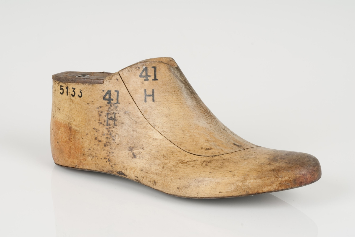 En tremodell i to deler; lest og opplest/overlest (kile). Høyrefot i skostørrelse 41. Såle av metall. Lestekam av skinn