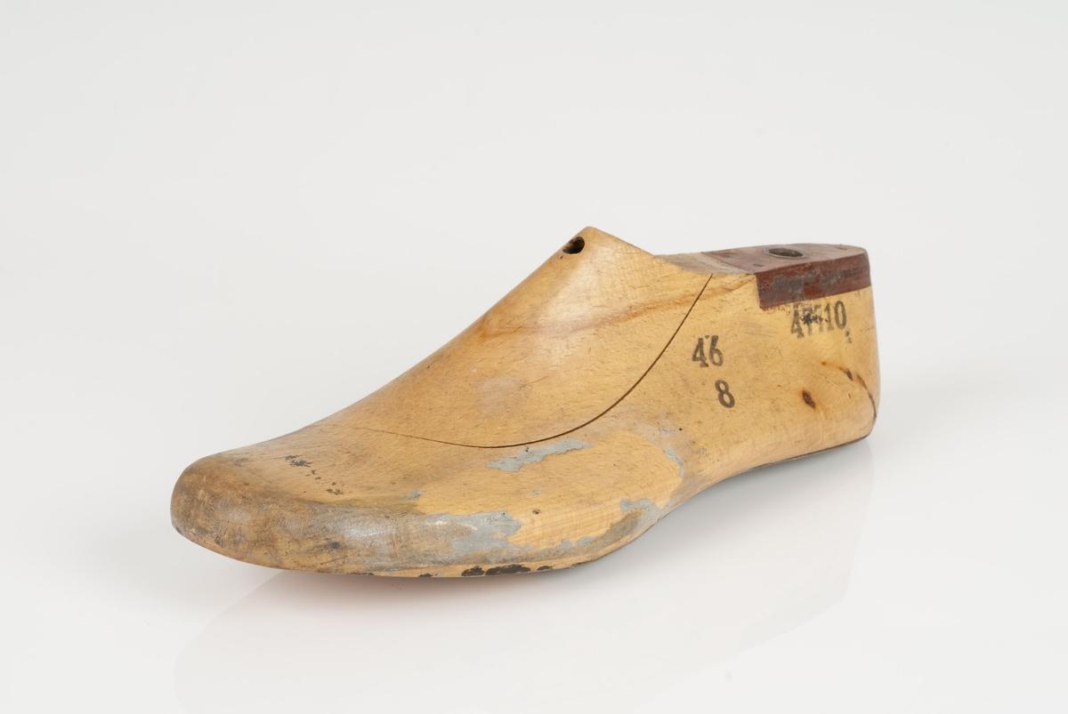 En tremodell i to deler; lest og opplest/overlest (kile). Venstrefot i skostørrelse 46, og 8 cm i vidde. Hælstykket og gelenken/svangen i metall. Lestekam i skinn.