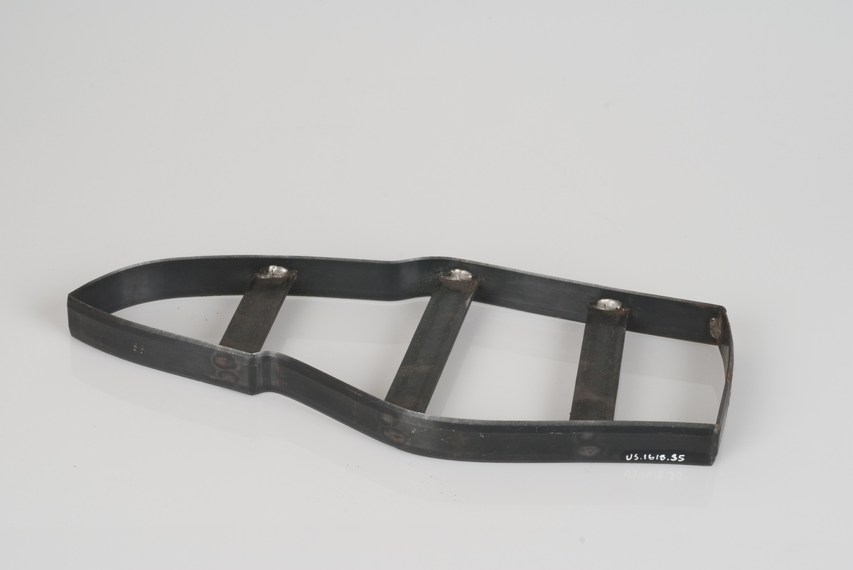 En stansekniv av stål. Stansekniven brukes til å stanse ut skodeler for sko i størrelse 33. Påklistret teipbit med påført tekst på stansekniven.