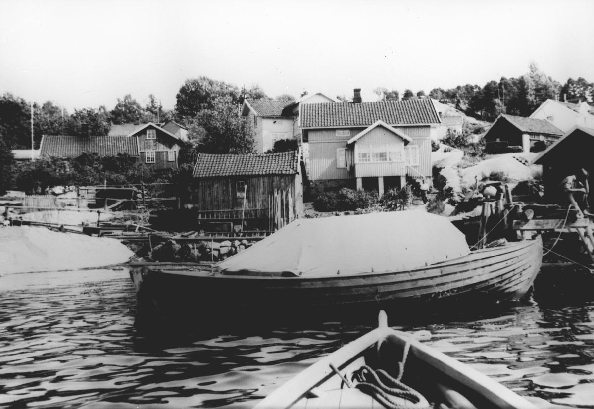 Trebåt i sjøen utenfor et tettsted.