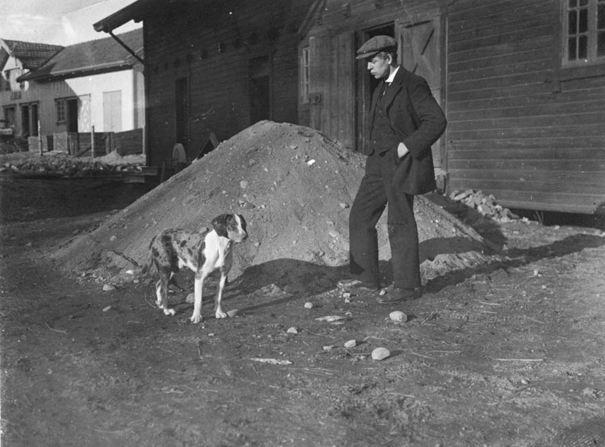 Uthuset Vanaheim. Bak uthuset til Refsum. Mann med hund.