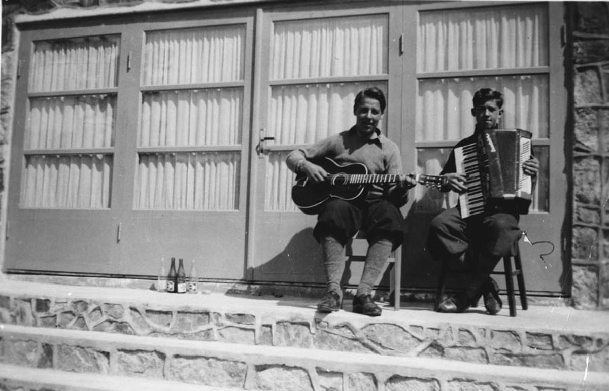 Gruppebilde. To menn spiller trekkspill og gitar.