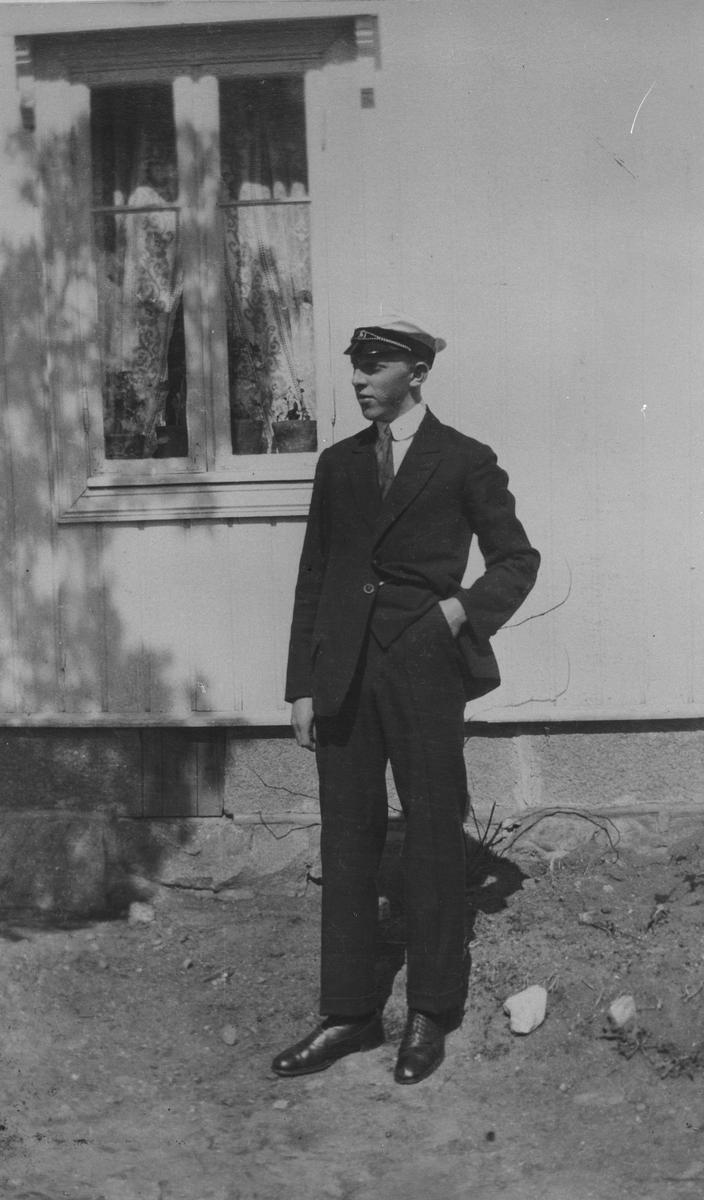Mann med uniformslue, foran hus.