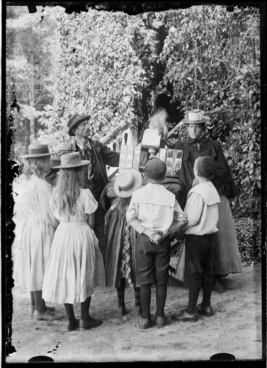 Omreisende fotograf med apekatt. Flere barn.
