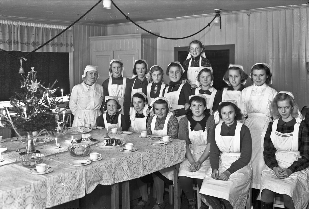 Jenter i hvite uniformer ved juletid. Sittende fra v.: X, X, Berntsen, Reidun Handegård, Astrid Olsen, Inger Johanne Hoel. Stående bak fra v.: X, X, X, X, Gunvor Bjørke g. Karlsen, X, X, X, X.