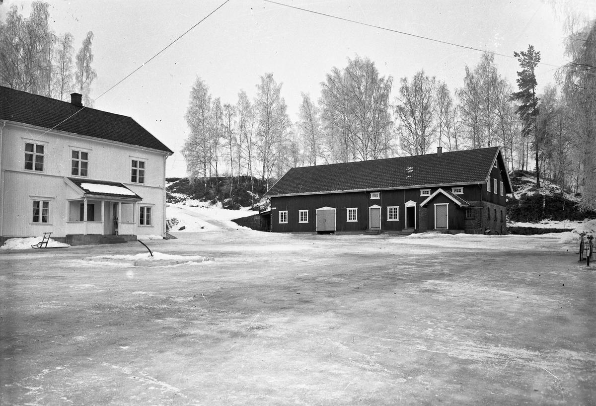 """Gårdsbruk. Skilt med """"Kvinner"""" og """"Menn"""" står over dørene på fjøset."""