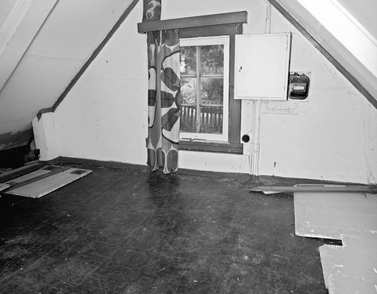 Interiør: loft, vindu med gardin på en side.