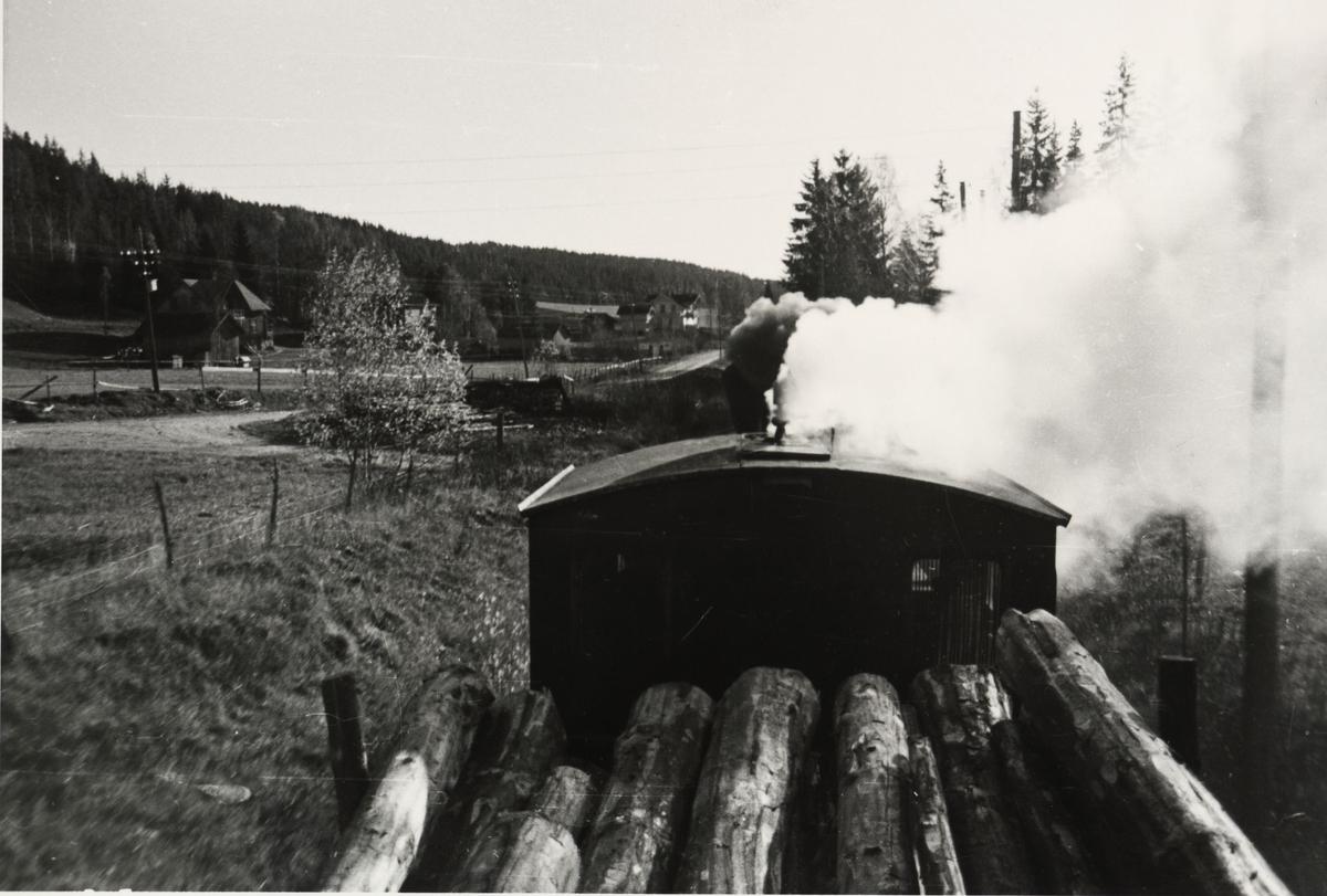 Tog til Skulerud. Fotografen sitter oppe på tømmeret på første vogn i toget. Nær Skulerud. Skulerud hotel i bakgrunnen.