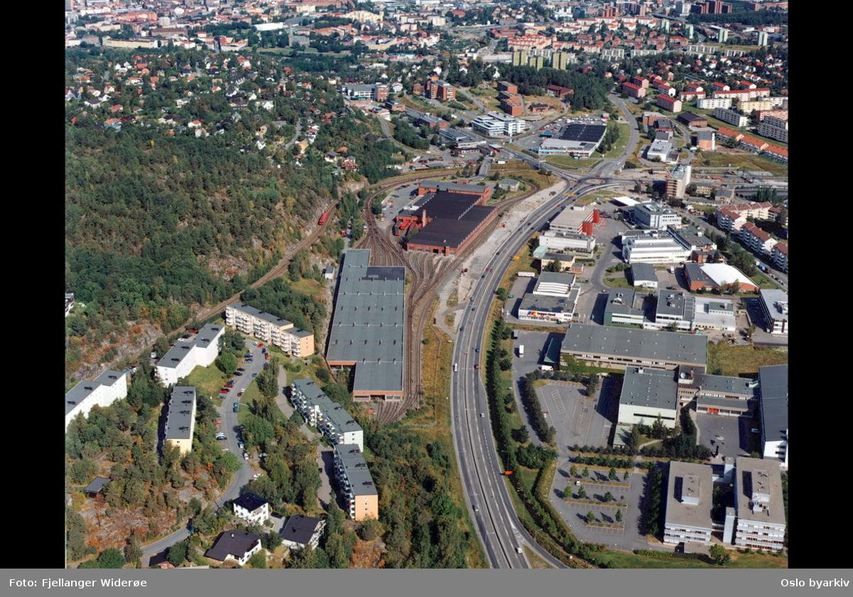 Enebakkveien, Europaveien (E 6), Vårveien, Ryensvingen. Ryenkrysset. Lambertseterbanen. Ryen industriområde. Vognhall / verksted for T-banen. Simensbråten og Manglerud nærmest i bakgrunnen. (Flyfoto)