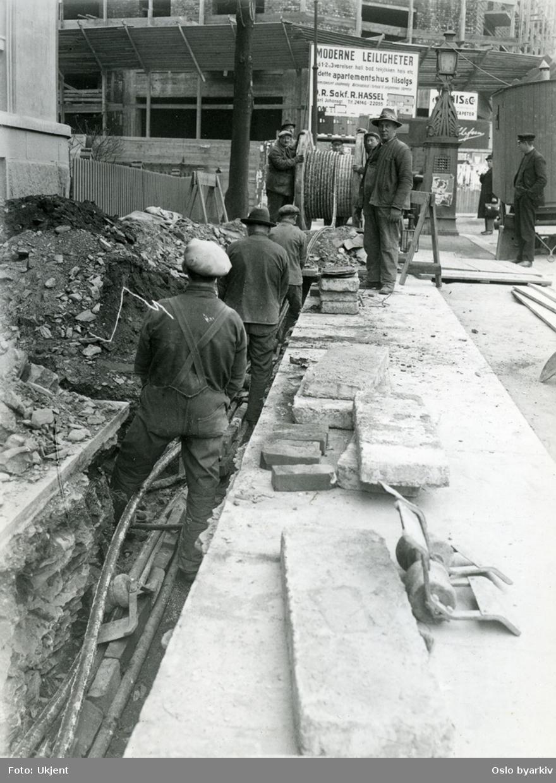 Arbeidere graver en grøft og strekker ut kabel i gata.