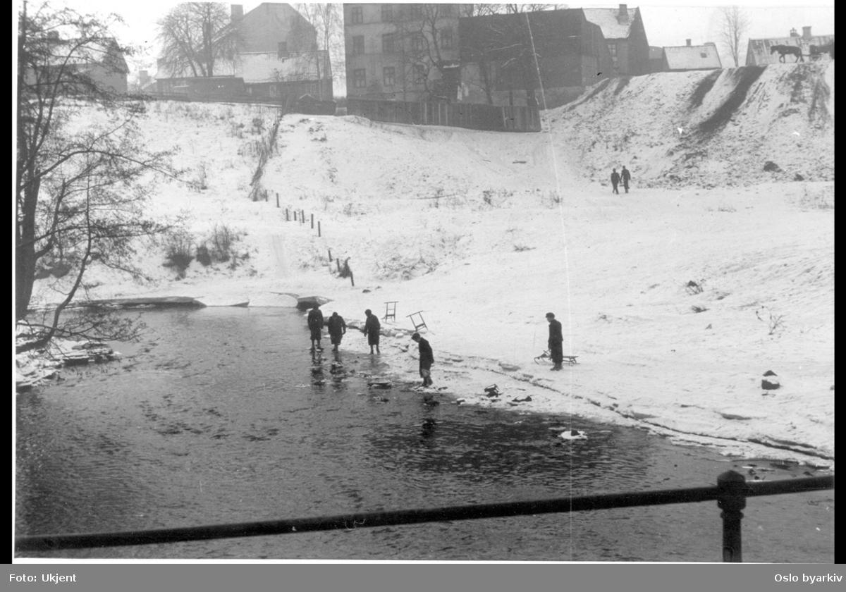 Gangbrua over Akerselva, fra Myrens verksted til Myraløkka (uopparbeidet parkområde), vestover mot den gamle begyggelsen i Maridalsveien (nr.159a midt i bildet) en vinterdag. Gutter med kjelke vader langs elvekanten. Øverst i høyre hjørne hest med vogn. Akebakker.