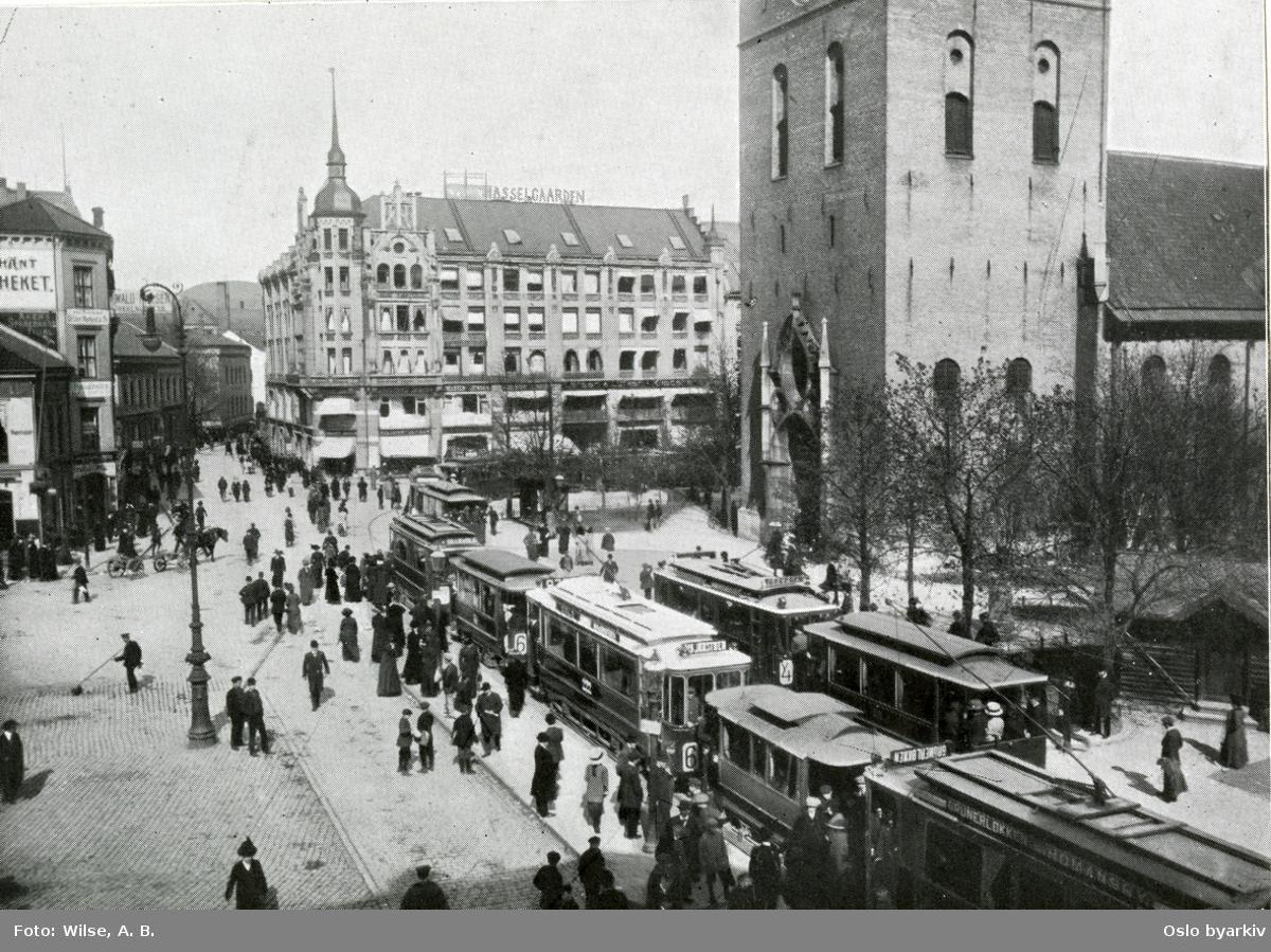 Trafikkmiljø ved Stortorvet utenfor Oslo domkirke med trikker / sporvogner ved stoppested. Hest og spaserende. Hasselgården bak i midten, litt av Elephant-Apotheket til venstre. Bilde brukt i kommuneberetningen fra 1887 - 1911.