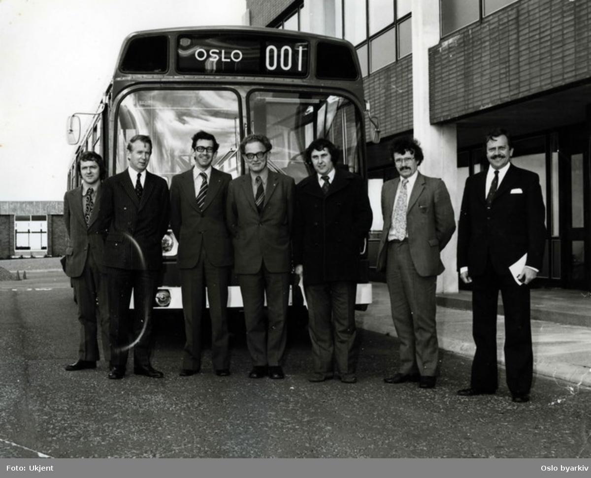 En Leyland National buss. En busstype som ble produsert mellom 1972 og 1985. Da som et samarbeidsprosjekt mellom National Bus Company og British Leyland. Gruppefoto av representanter fra leverandør og mottaker. I midten står ingeniør Orre.
