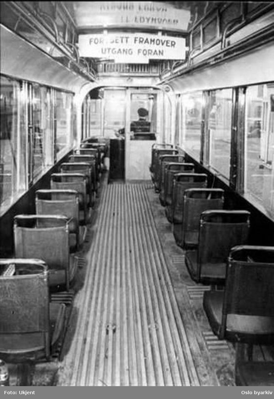 Oslo Sporveier. Trikk motorvogn 83 type SS lang (fra 1913), modernisert seteinteriør sett bakfra i passasjervogn. Vognfører.
