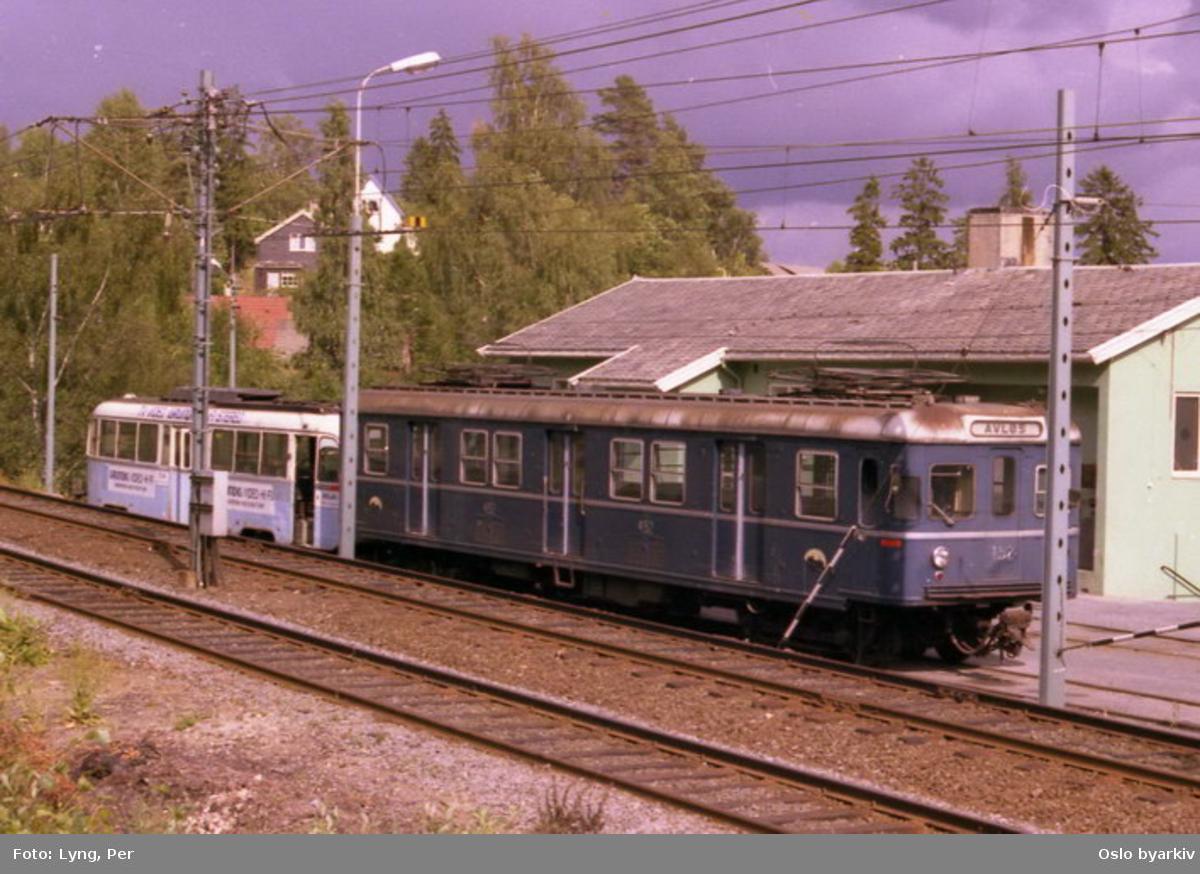 Oslo Sporveier. Trikk motorvogn type Gullfisk og T-banevogn 452 (fra 1960). (Den ene av sporveiens første vogner ment for T-banedrift, sammen med vogn 451, i ordinær trafikk på Kolsåsbanen, opphugget 1994.) Her avstilt på baneavdelingens tomt på Durud. Bilde tatt en gang mellom 1985-1990.