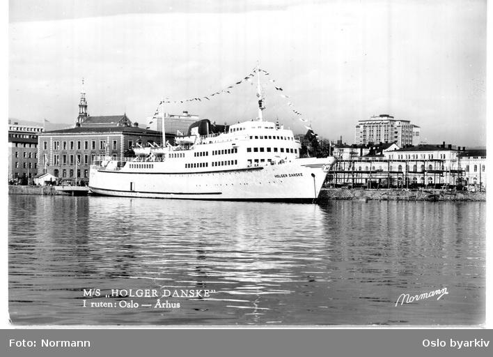 DA NO Linjens båt Holger Danske ved bryggeterminalen, Palékaia, ved Tollboden og Østbanebygningen. Gikk ruten Oslo-Århus via Horten fra 1961, fra 1974 til Fredrikshavn. Muligens fra jomfruturen, flaggprydet. Postkort.