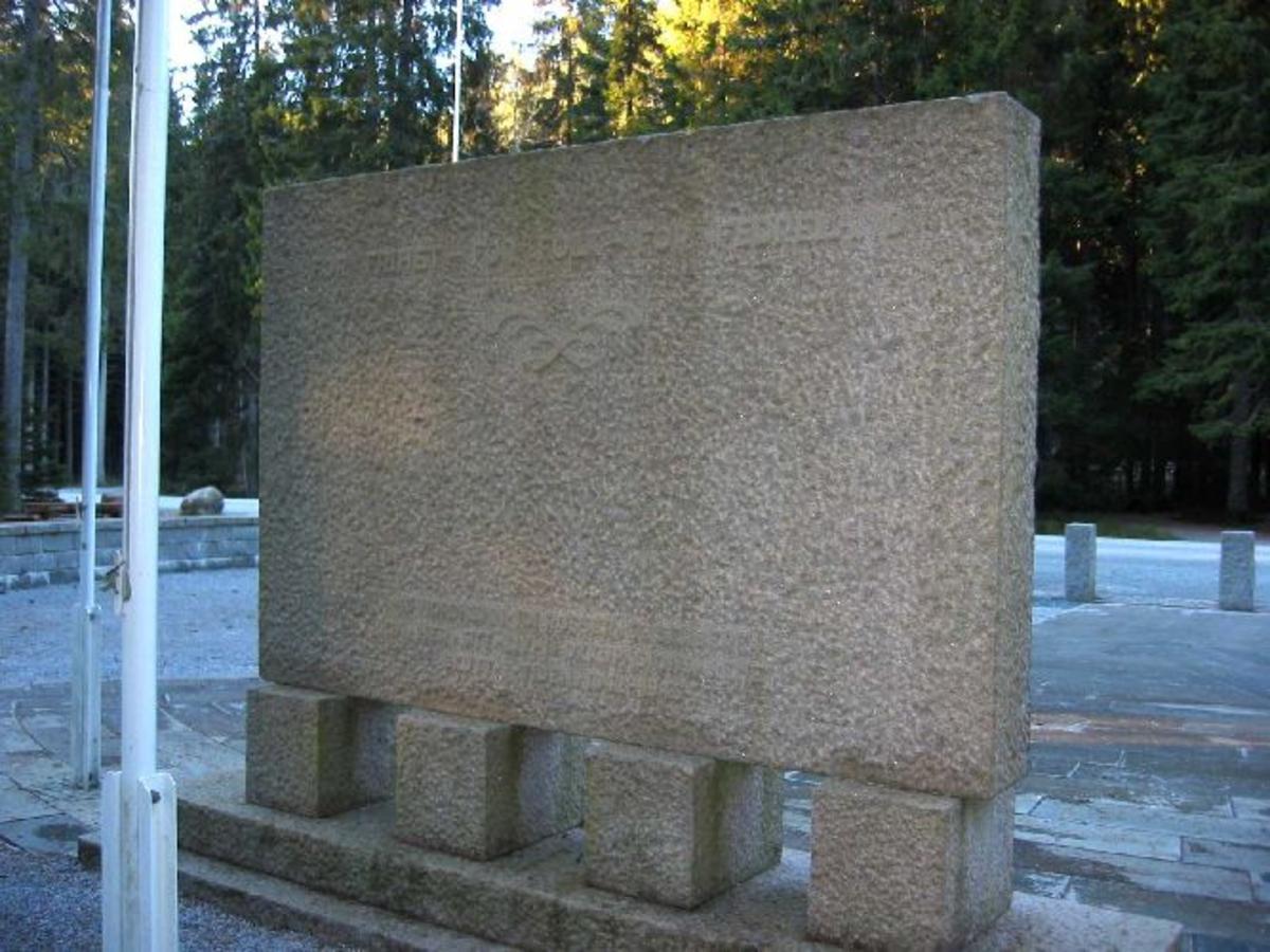 Skulptur/stein med relieff av henrettelse på forsiden, inskripsjon på baksiden plassert i et inngjerdet område.