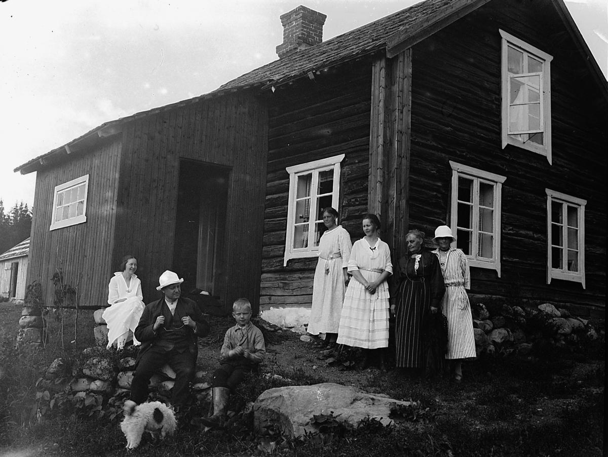 Gruppe utenfor tømmerhus. Eivind Olssøn sittende foran. I Atfor, Helgøya.