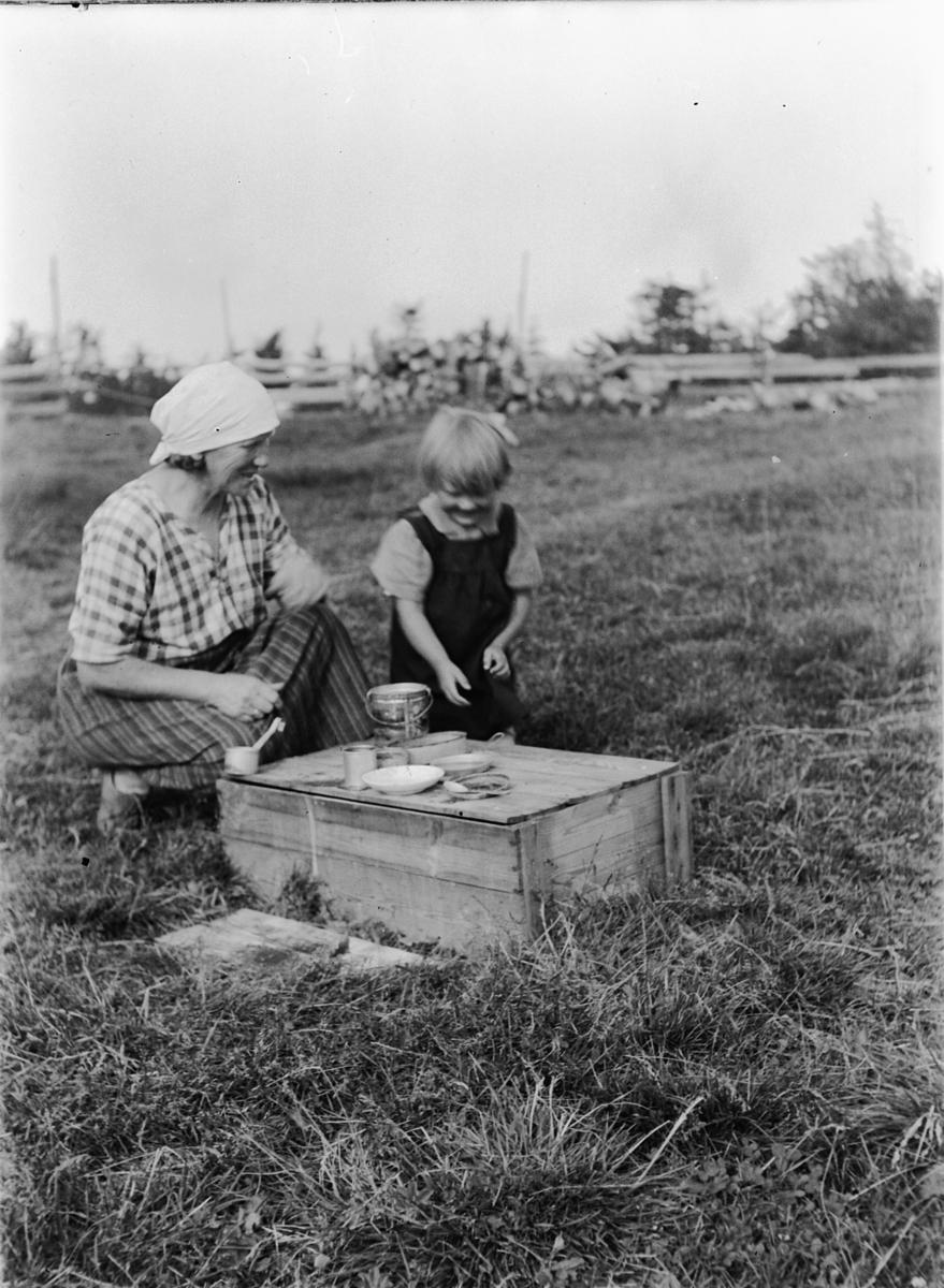 Ukjent kvinne og jente. Sitter ved ei kasse på jordet, leketøy, service. Datteren serverer mat til mor?
