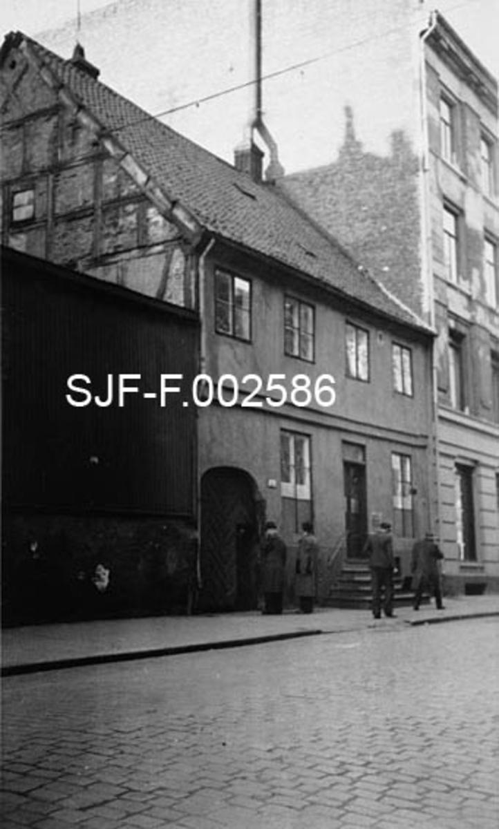 Skippergata 17 b, der Schwencke & Co's Eftf. hadde sitt forretningskontor.  Gården er oppført i to etasjer og har pusset, umalt fasade.  Bygningen hadde et forholdsvis bratt, krumsteinstekket saltak.  Gavlveggen, som vi ser den øvre delen av, var utført i utmurt bindingsverk, noe hele gården sannsynligvis var, uten at dette utvetydig lot seg lese av fasaden mot Skippergata slik den så ut da dette fotografiet ble tatt. Opp til inngangsdøra til ekspedisjons- og kontorlokalene var det ei fire-fem trinns trapp.  Foran denne trappa passerte et par frakkekledde fotgjengere på fortauet.  På hver side av døra igjen var det høye, seksruters vinduer.  I etasjen over var det fire fireruters vinduer.  Til venstre for kontorinngangen var det en rundbuet åpning mot et portrom.  Porten er stengt med ei kraftig tredør, med et mindre innfelt dørblad for personinngang.  Foran denne døra står et par menn. Til venstre for portrommet sto et bordkledd skur på en høy mur.  Til høyre for Skippergata 17b sto en fire etasjes teglsteinsgård av den typen det ble bygd så mange av de siste tiåra på 1800-tallet.